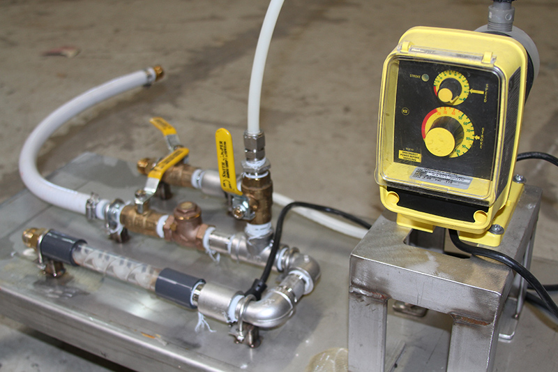 A metering pump connected to pipes and hoses on a liquid polymer dosing skid.