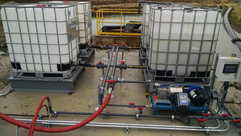 Four liquid polymer totes connected to a liquid polymer dosing skid setup next to a settling pond.