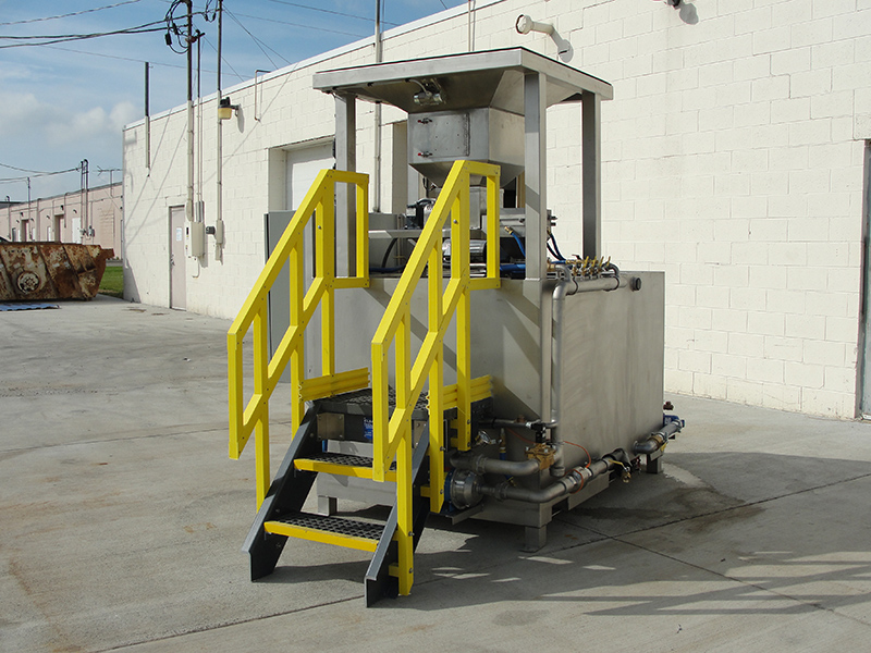 Clearwater Industries Model 300 Stainless Steel Big Bag make-down polymer system displays it's staircase and big bag pan that holds bag over the polymer hopper.