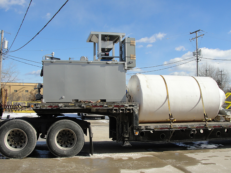 Clearwater Industries Model 500 Stainless Steel Big Bag polymer make-down system pictured from the side while on a semi-truck bed before it leaves for delivery.