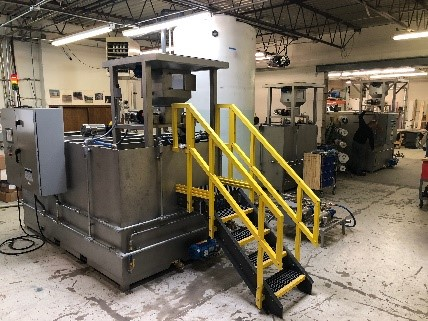 Clearwater Industries Model 800 Stainless Steel Big Bag polymer make-down system pictured in the manufacturing department and displaying the big bag pan that holds it above the hopper.