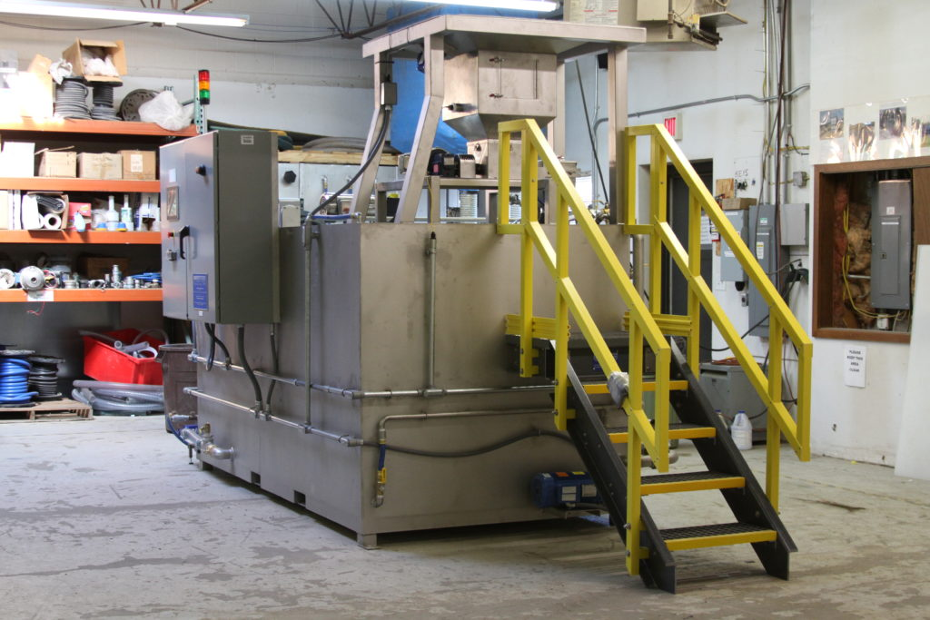 Clearwater Industries Model 800 Stainless Steel Big Bag polymer make-down system pictured in the manufacturing department and displaying the big bag pan that holds it above the hopper, it's control panel and operator staircase.