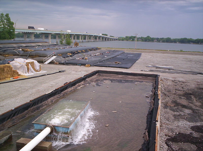 Treated water at an environmental clean-up site is pumped into dewatering bags.