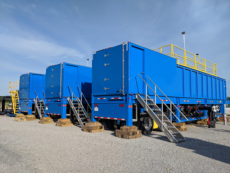 Three blue portable clarifiers lined up in a gravel parking lot.