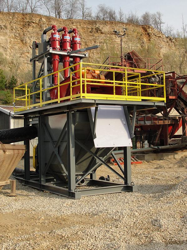 A stationary fines recovery system with three red cyclones, yellow railing and a grey tank.