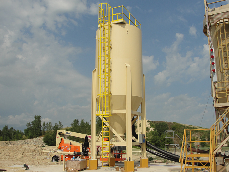 A tan industrial high compaction water clarifier setup at an aggregate production site.