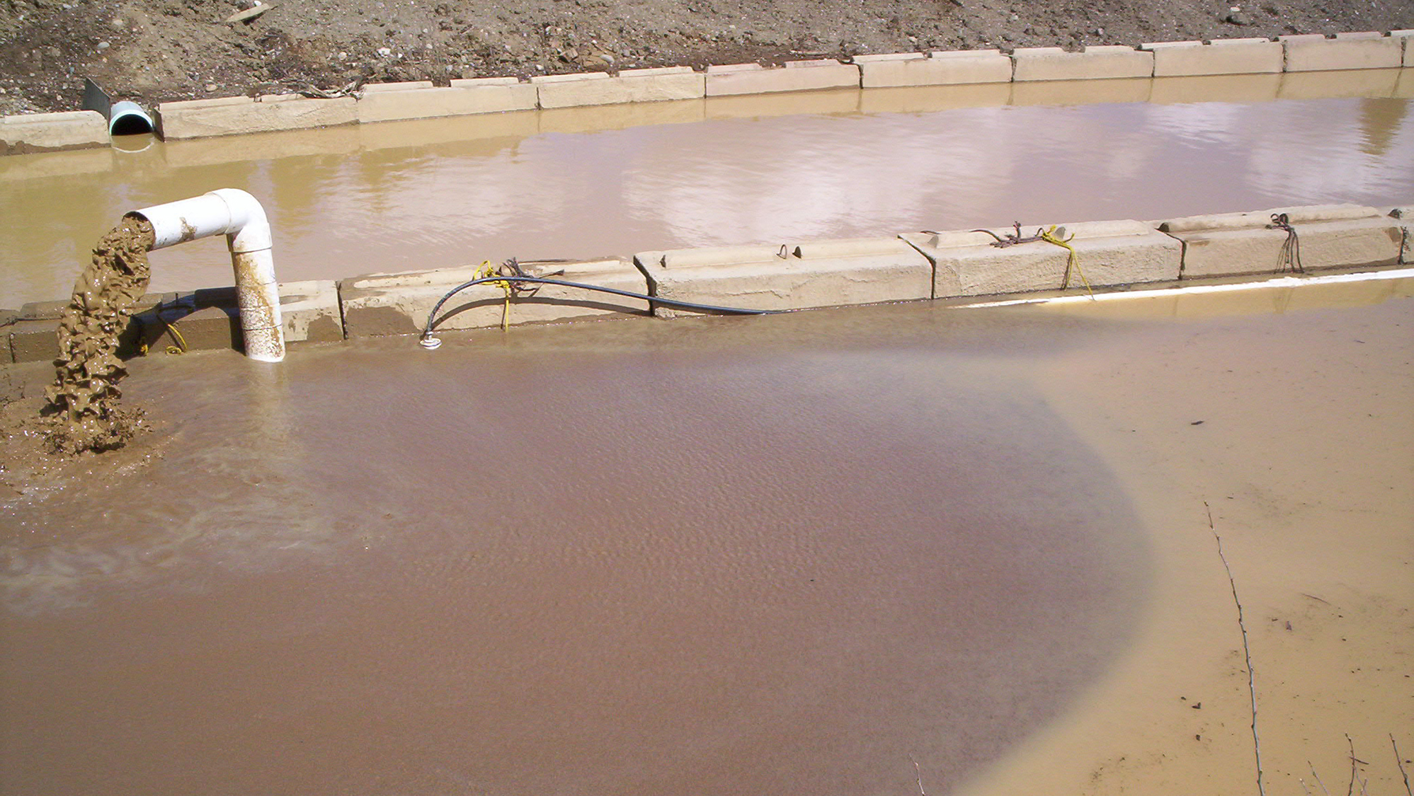 Dirty water pumping out of a pipe into a dirty water cell with another dirty water cell filled behind it.