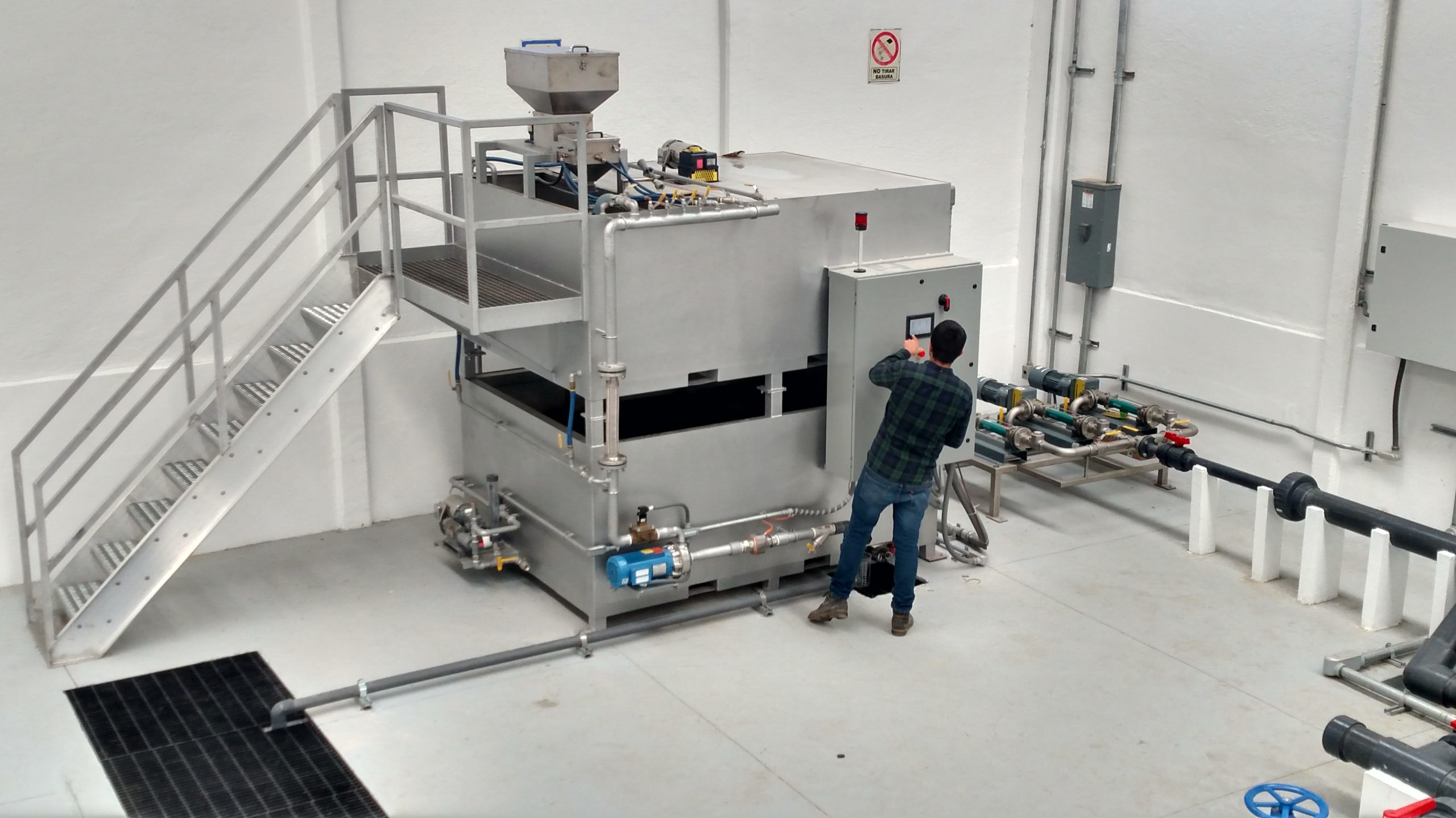 A man programming the control panel of a large stainless steel dry polymer preparation system that has two tanks.