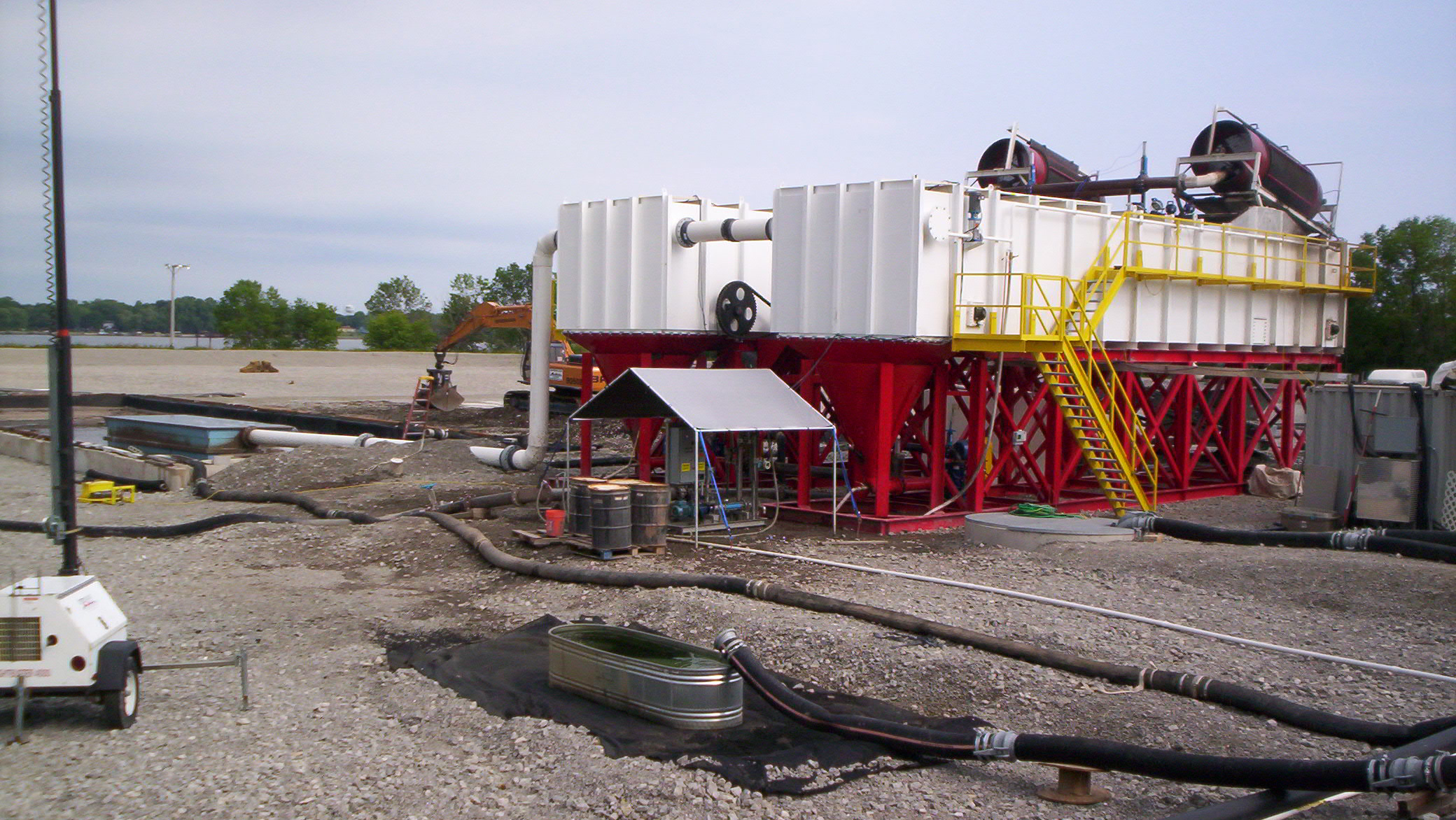 Two large industrial rectangular clarifiers at a dredging job site.