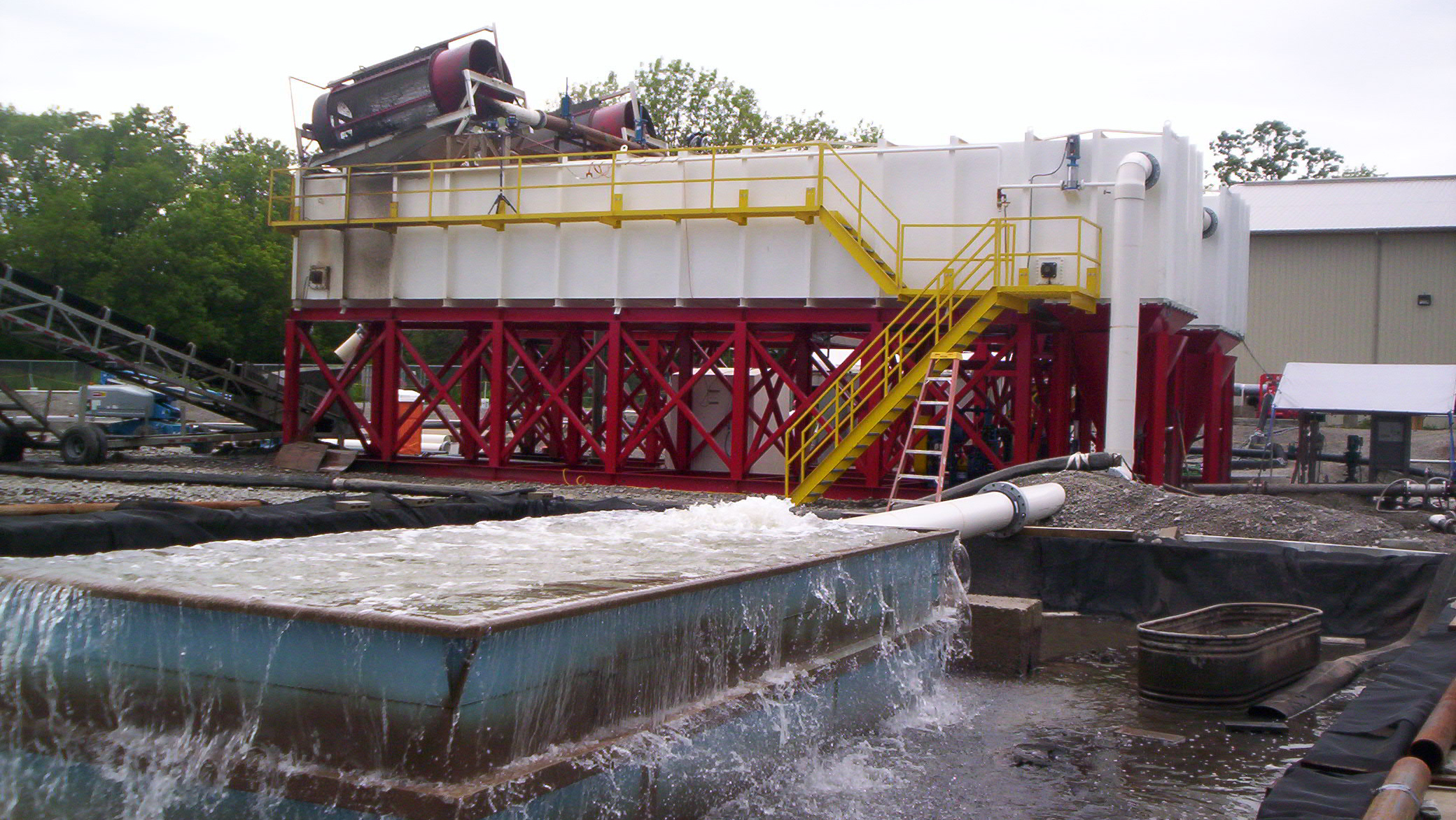 Large rectangular clarifiers in the background with rotary trommel screens on top of them and a clean water overflow basin in the foreground.