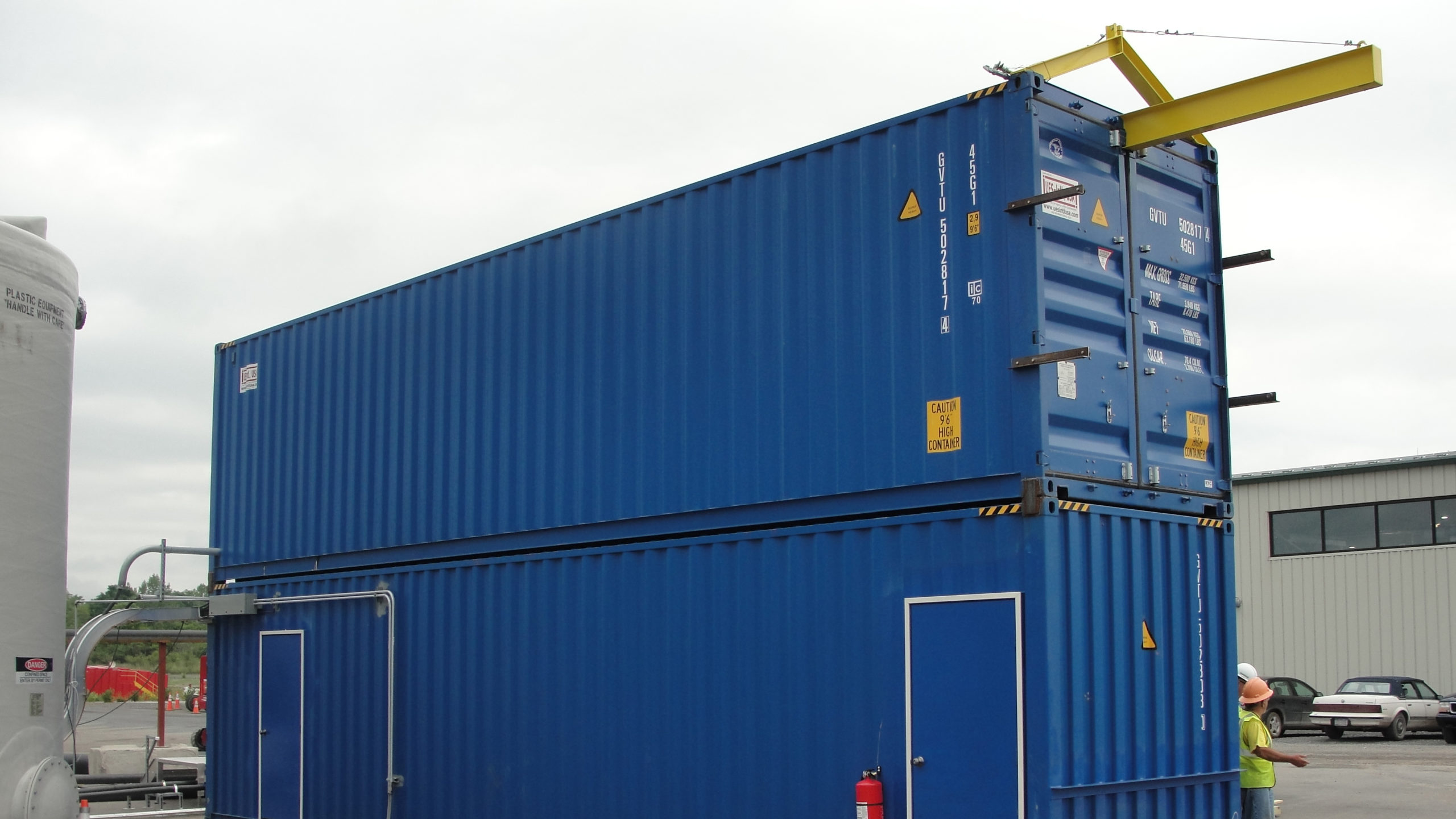 Two shipping containers stacked on top of each other and connected to house a dry polymer preparation system for a dredging project.