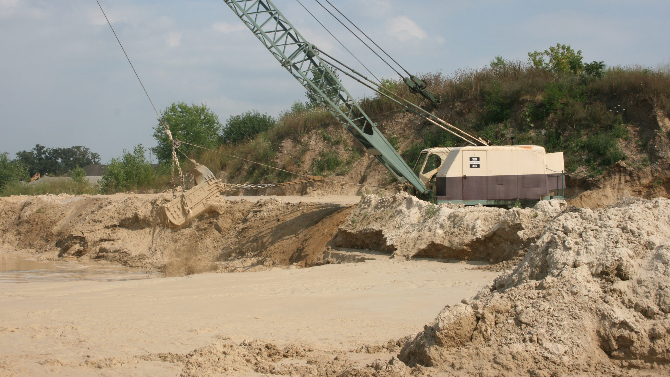 A tan and brown dragline crawler crane dredging a pond with stacked sand in the foreground.