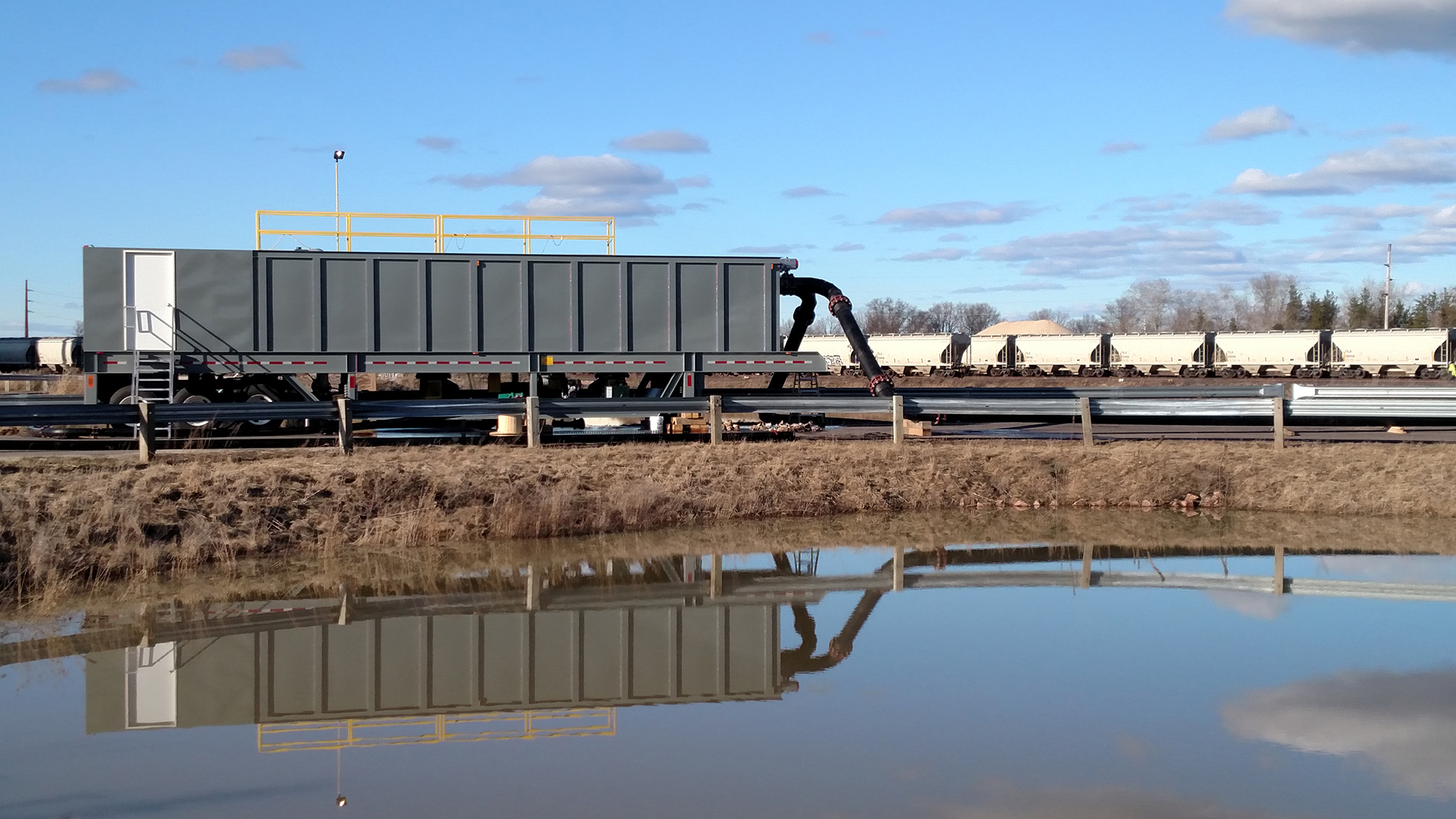 A grey rectangular portable water clarifier cribbed up next to a stormwater holding pond with a train in the background.