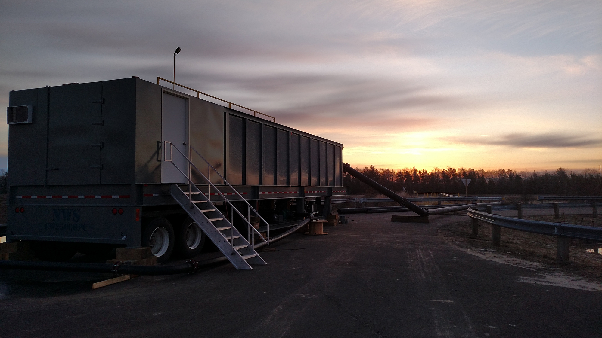 A portable water clarifier with stairs going up to a white door on the back of the clarifier and a sunset in the background.