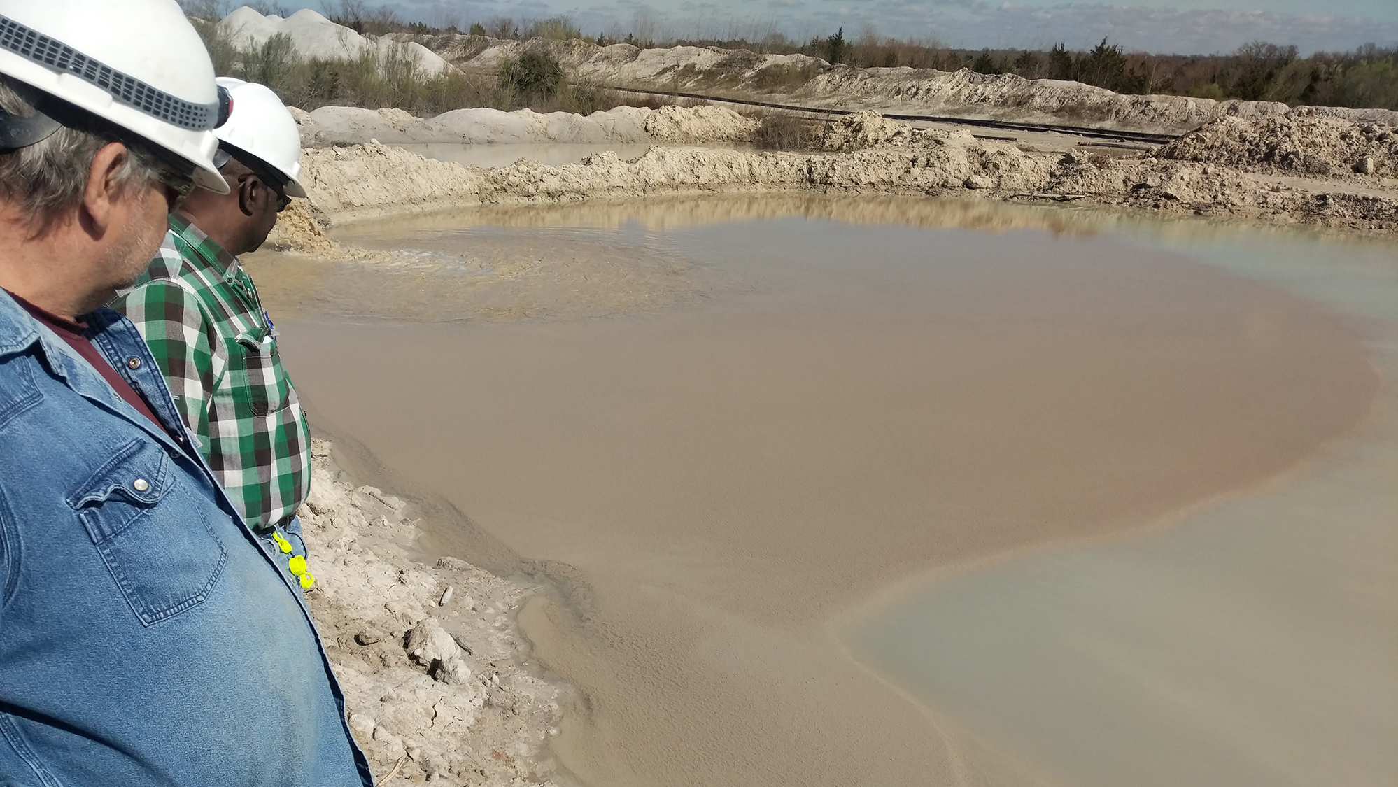 Two men in hard hats looking at dirty water discharging into a settling basin.