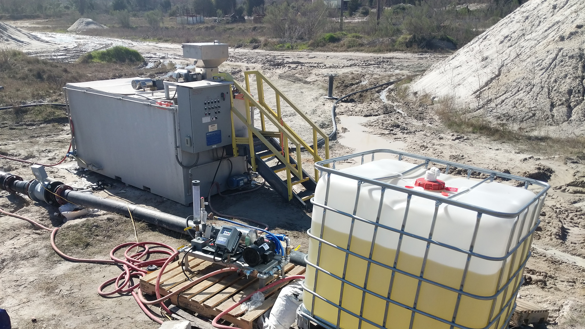 A tote holding unidentified liquid with a liquid polymer skid and a dry polymer preparation system setup in the background at a sand and gravel facility.