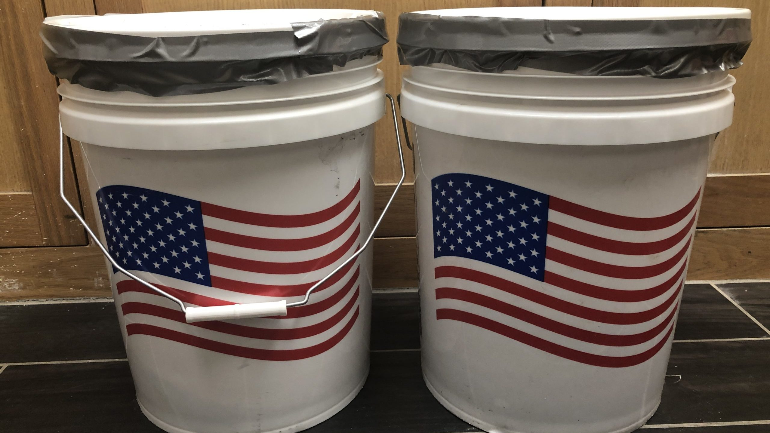 An image of two 5-gallon buckets with american flags on them.