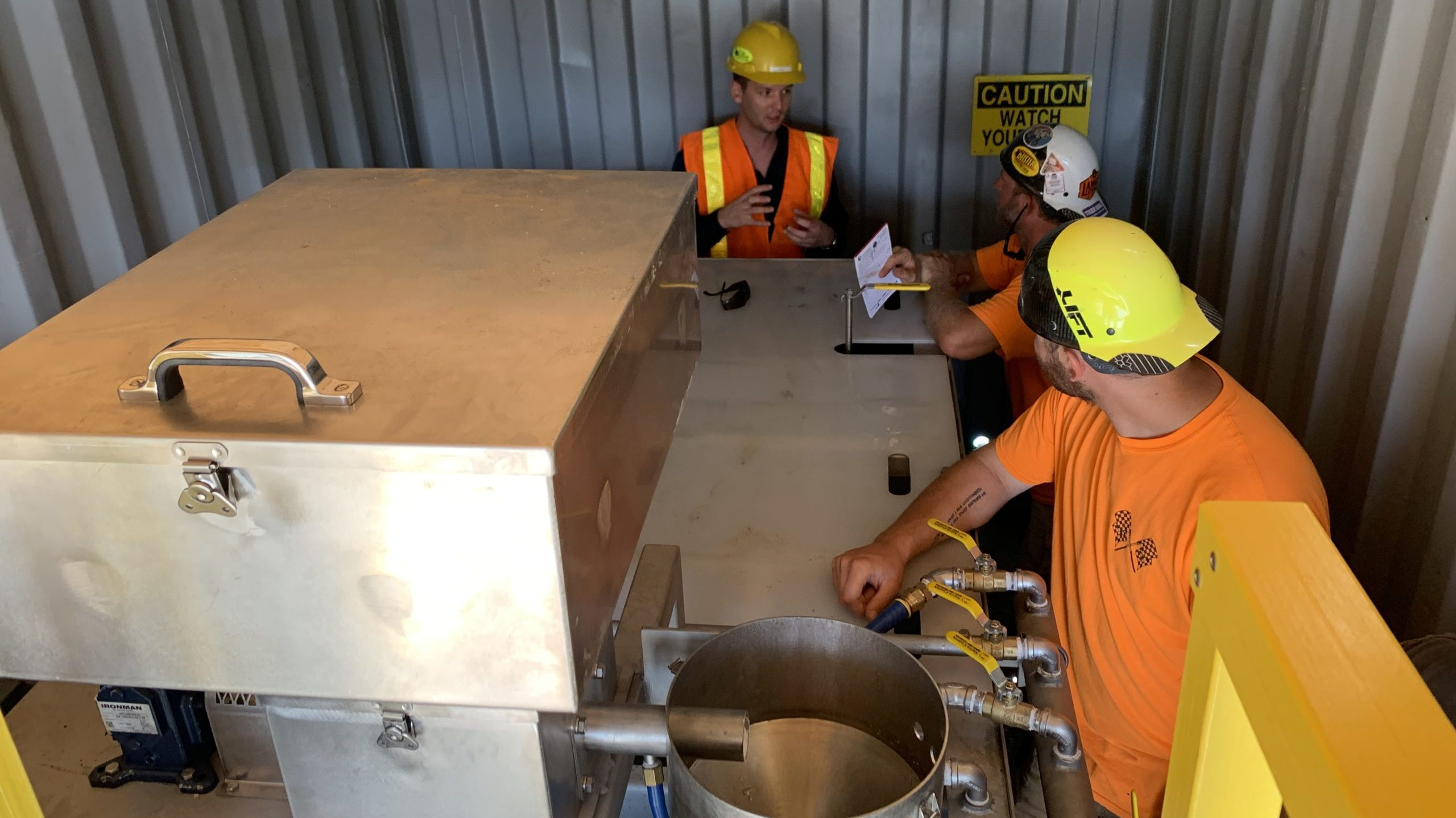 A clearwater employee is training two men how to use Clearwater's polymer batching system