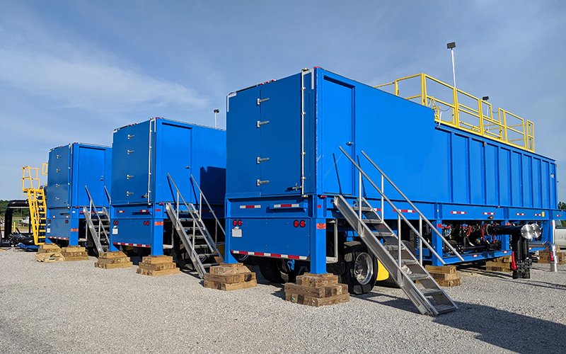Three blue portable water clarifiers cribbed up outside at a job site.