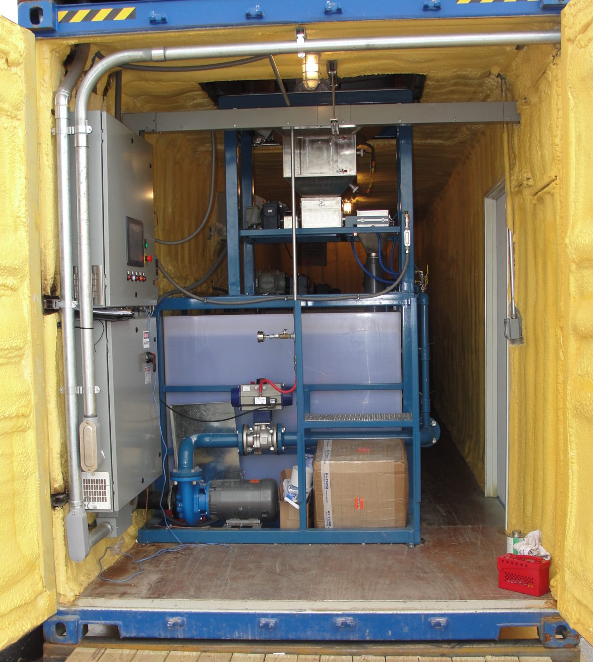 A dry polymer preparation system in spray foam insulated and climate-controlled shipping container.