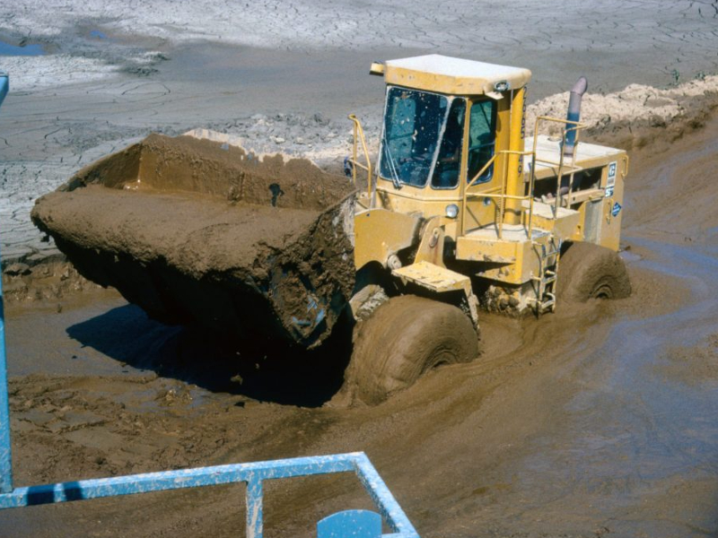 A picture showing a backhoe loader cleaning sludge out of a settling pond.