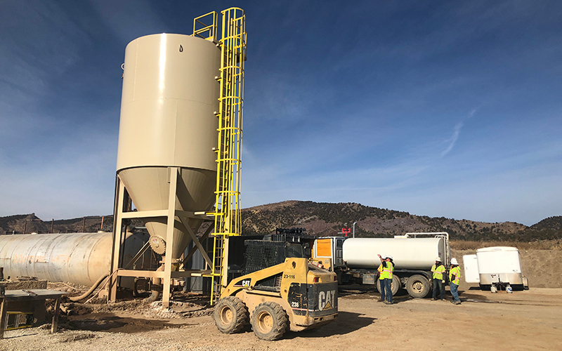 A tan stationary high compaction water clarifier, CAT skid steer loader, water truck and workers in hi-vis vests outside at an aggregate production site.