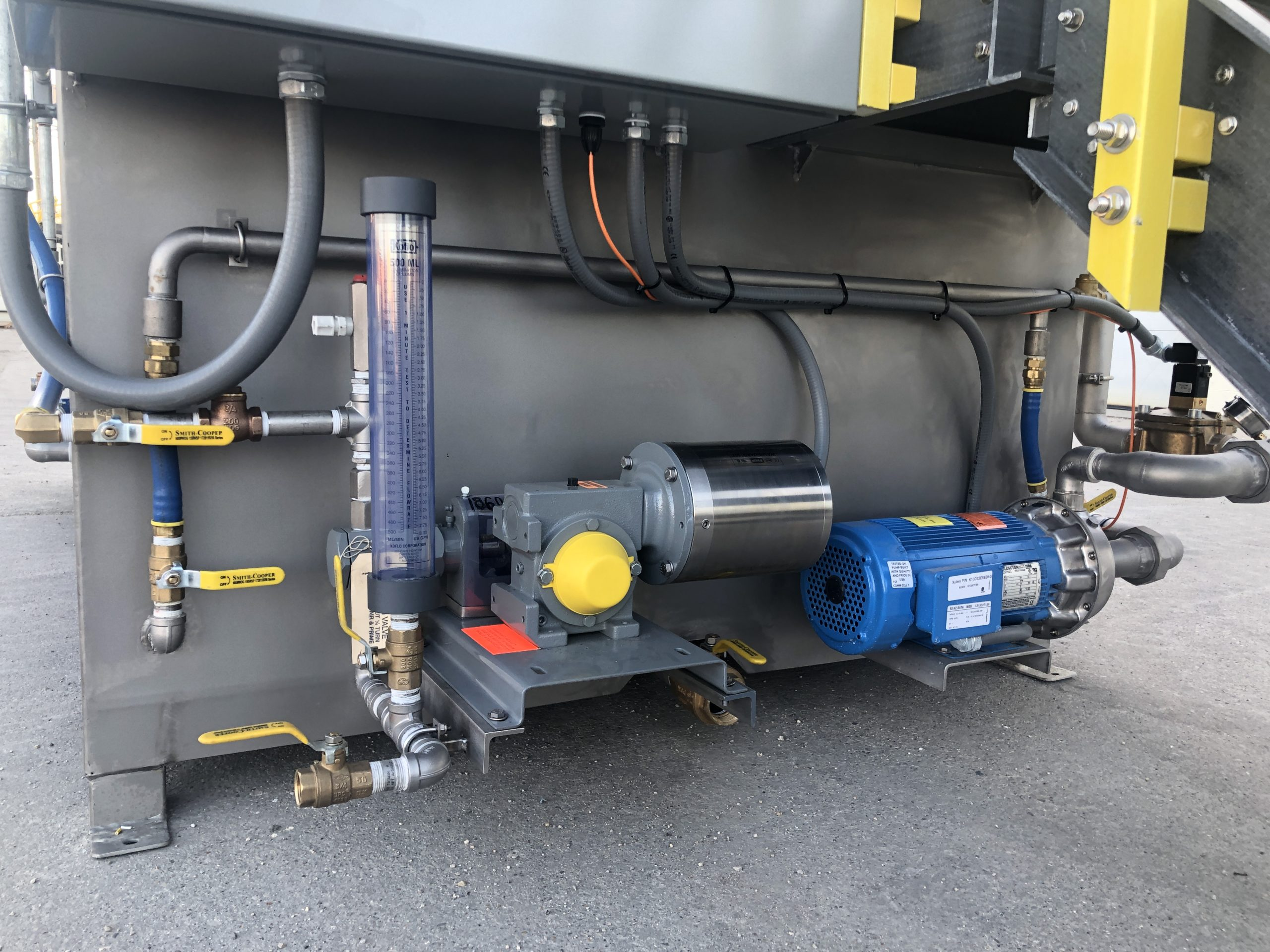A close up vies of the liquid polymer calibration column and pump that is attached to the larger bodied dry polymer system.
