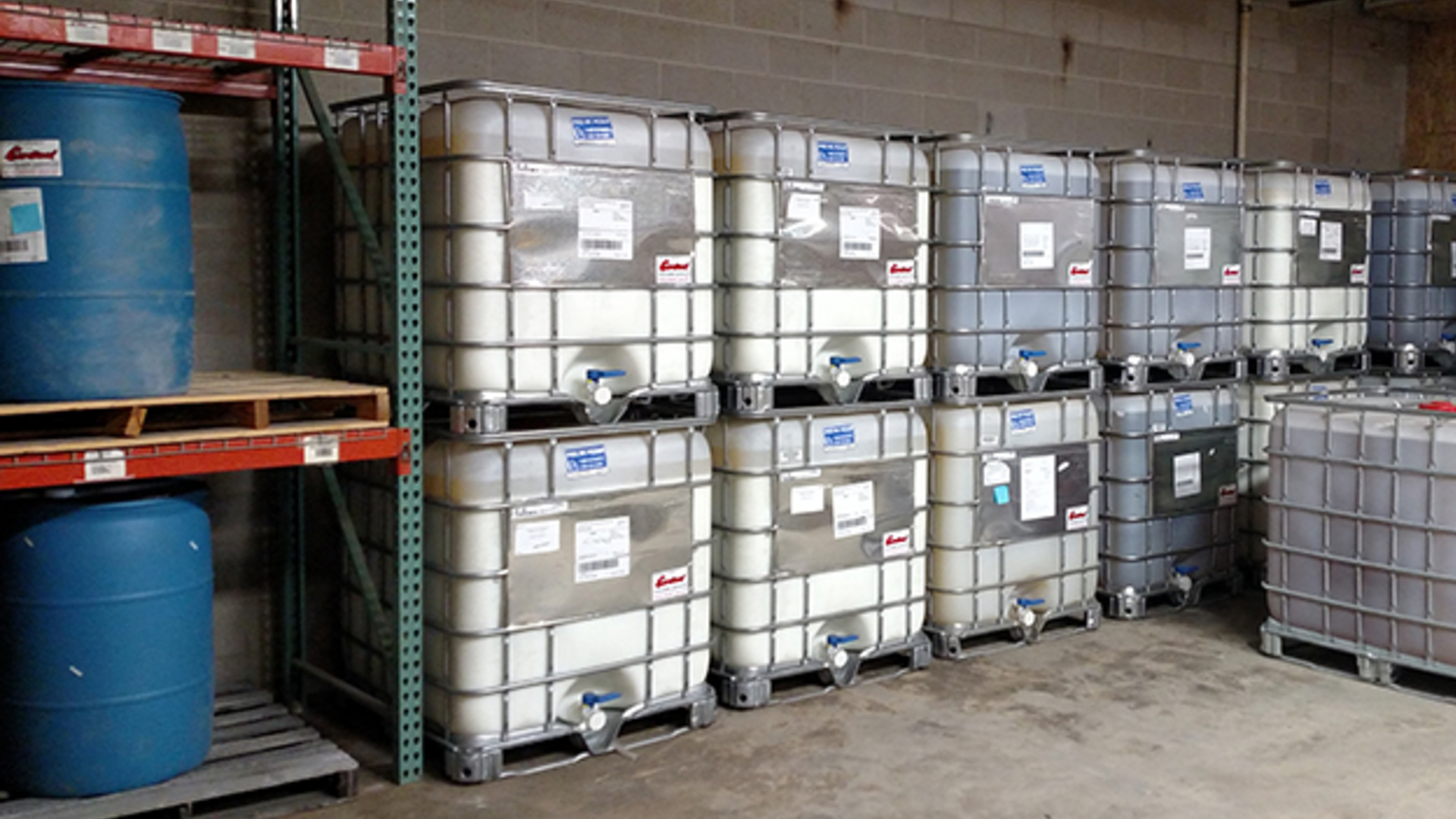 A picture showing liquid polymer totes stacked on top of each other and liquid polymer drums on shelving in a warehouse.