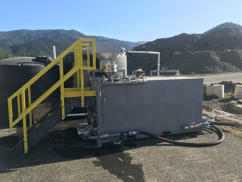 The side of a dry polymer unit at a sand and gravel site with water tanks behind it and mountains in the background.