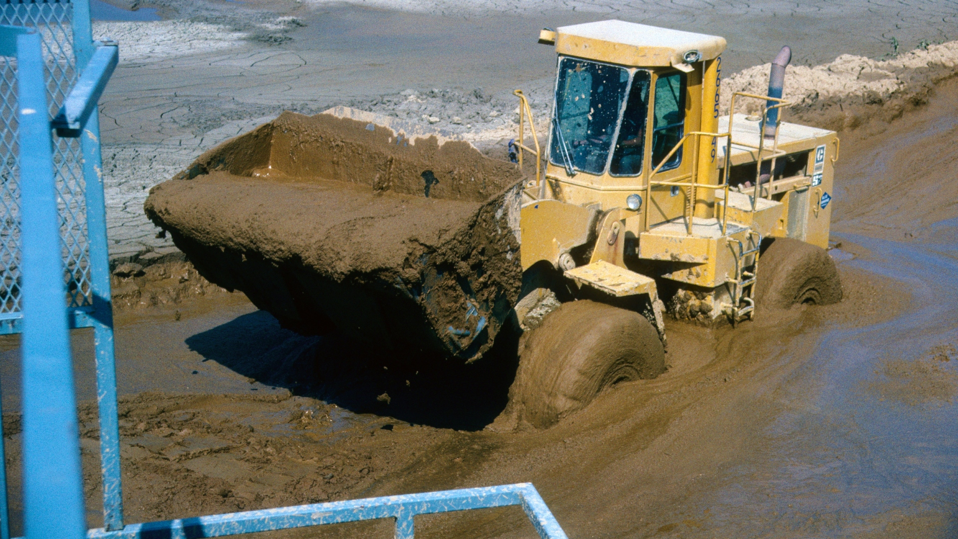 A front loader driving through a muddy settling pond with a watery bucket load.