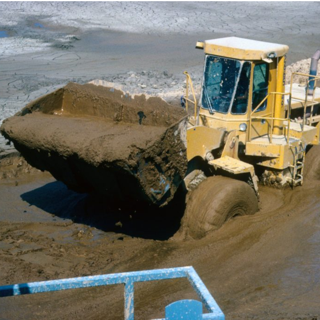 A front loader driving through a muddy pond with a bucket of soupy mud.