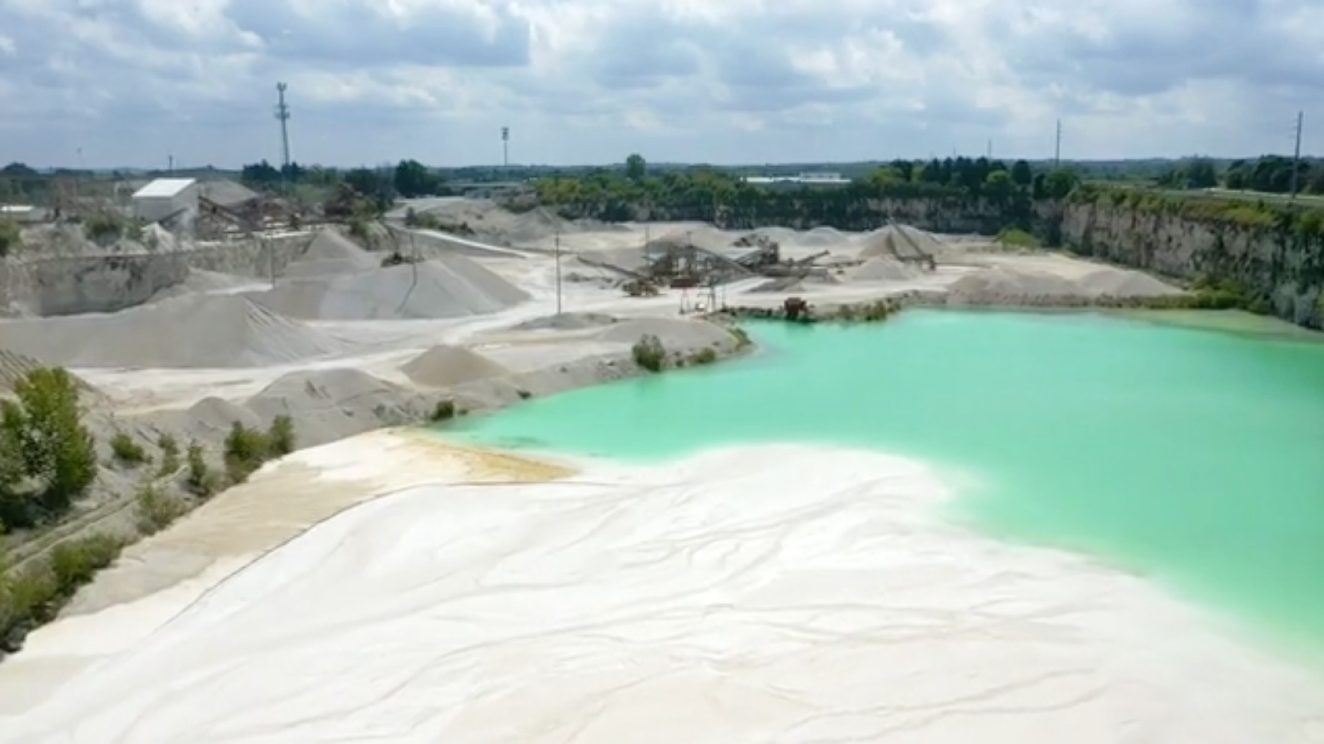 A drone photo of a limestone quarry showing the machines and ground stone in the distance and the settling pond in the foreground.