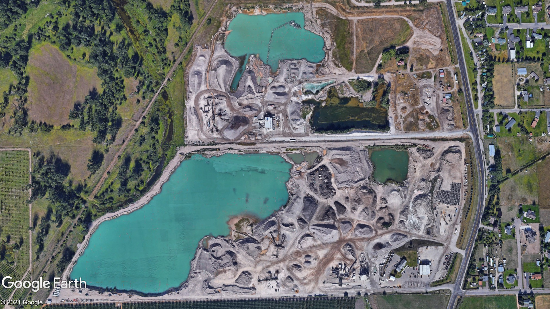 A satellite image showing an aggregate production site with large ponds and rock piles.