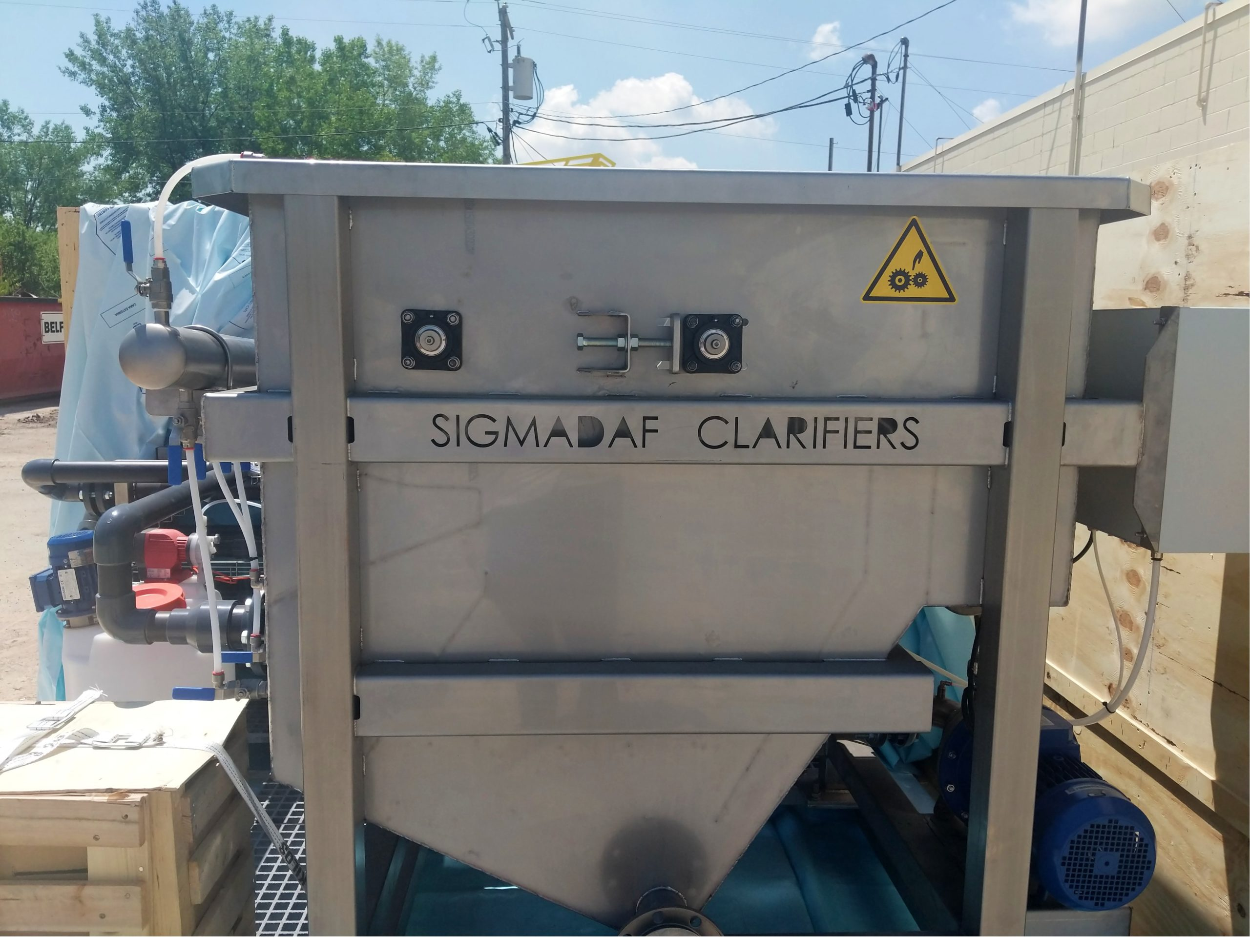 A large stainless steel tank pictured outside with SigmaDAF Clarifiers stamped into it.
