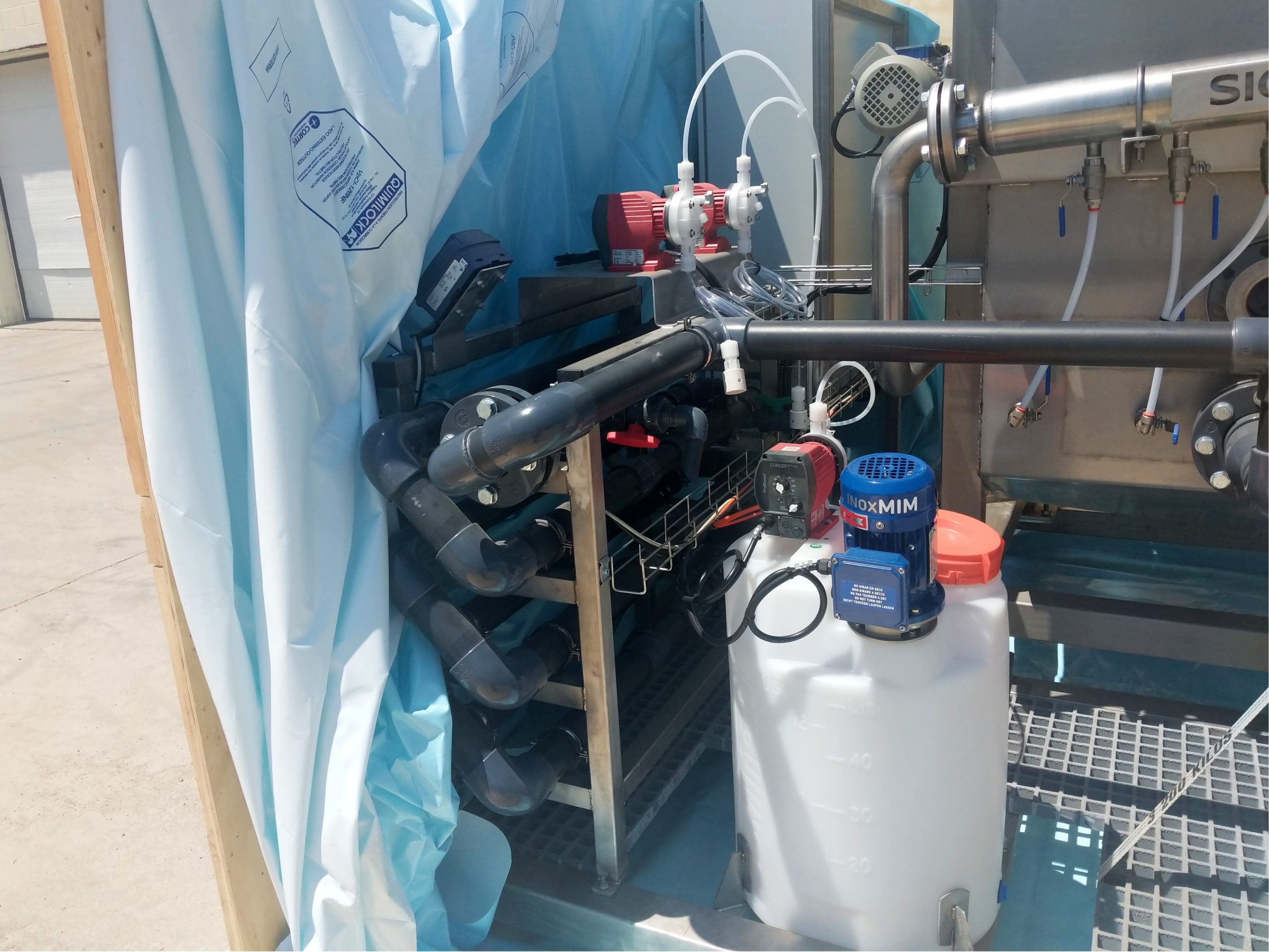 Flocculator tubes and a polymer preparation tank on a DAF skid that was just unpacked from its shipping crate.