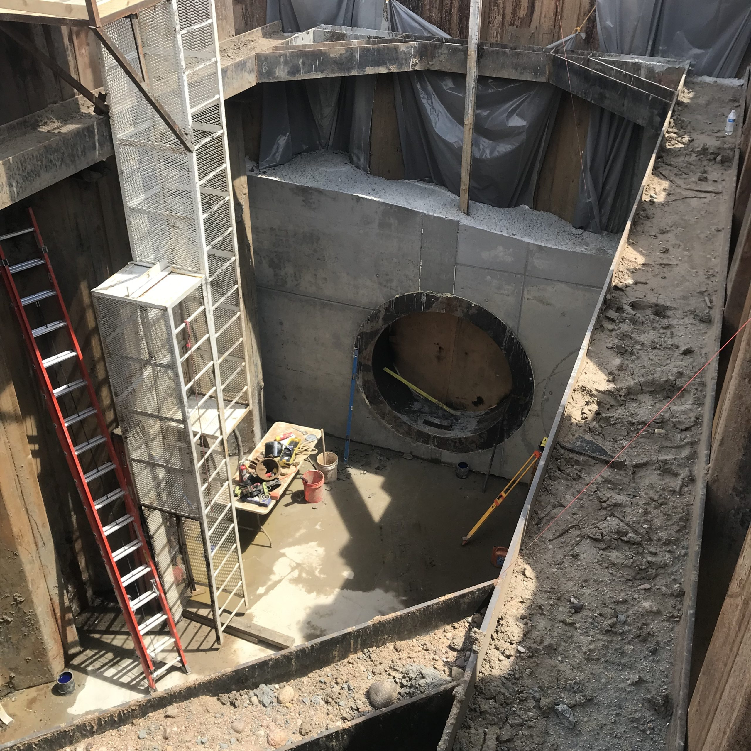 A large pit in the ground with ladders, buckets and other equipment where a drilling and tunneling machine will begin its work.