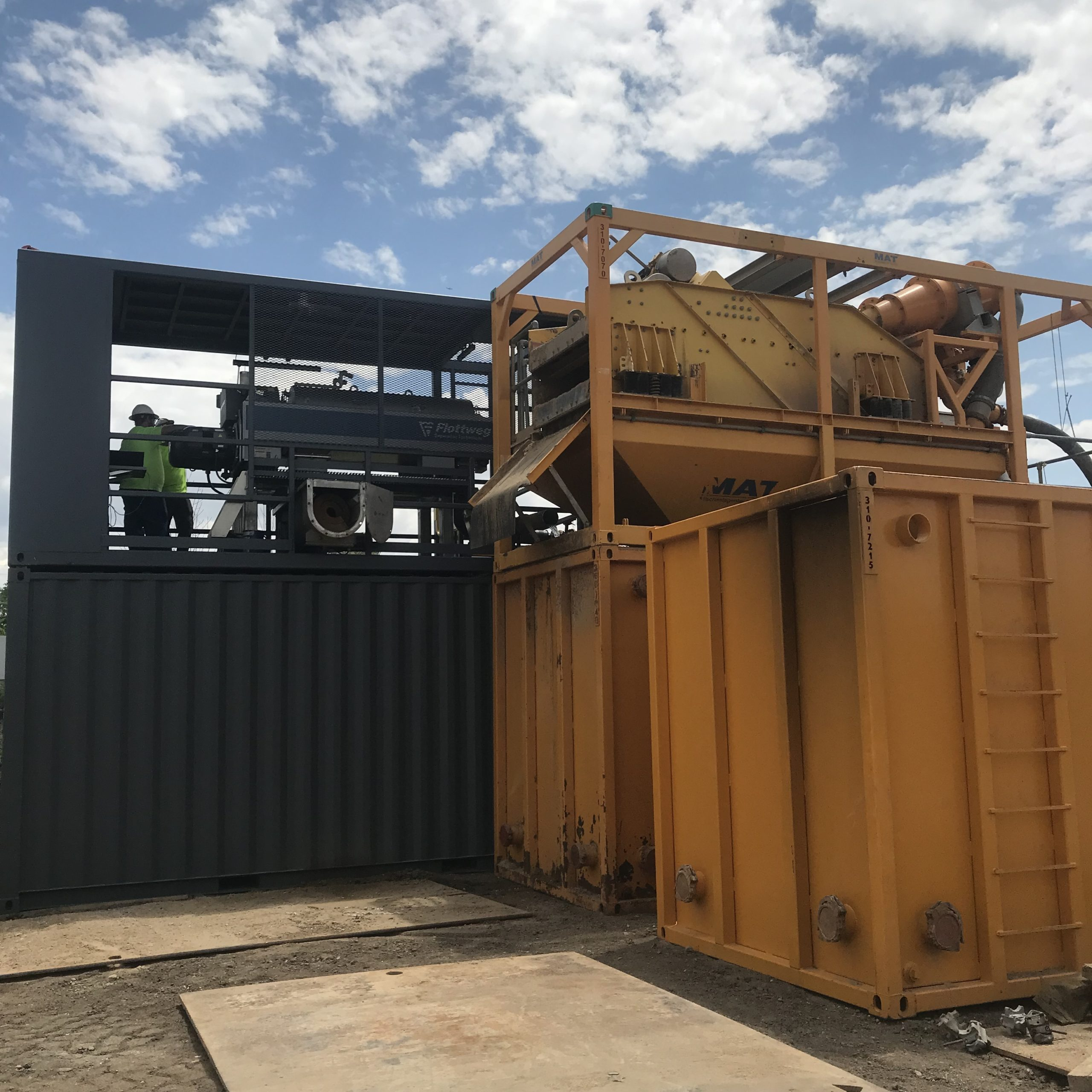 Large yellow containers next to a large grey container where two men stand next to a centrifuge on top of the grey container.