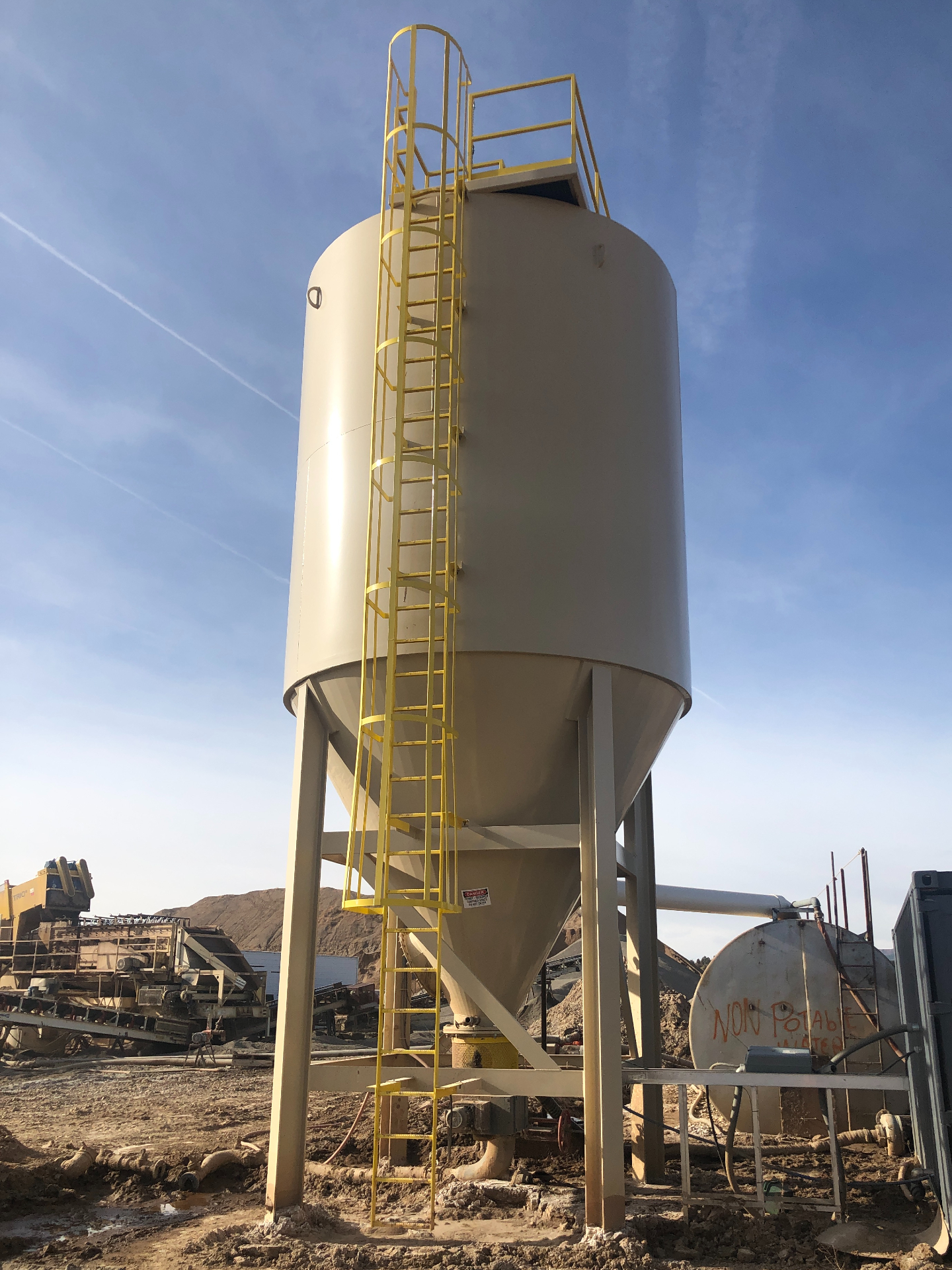 A tall slurry thickener setup at an aggregate production pit.