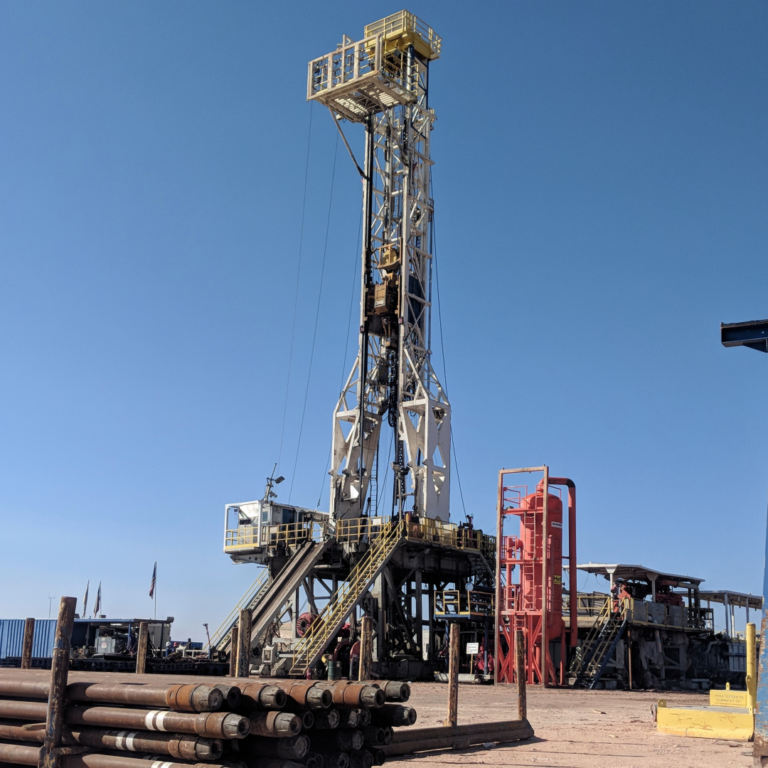 A drilling rig setup on land with drilling pipes in the foreground.