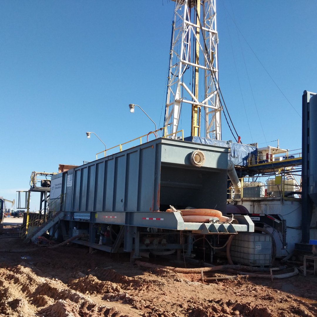 A rectangular portable industrial water clarifier pictured at an angle with a drilling and tunneling rig in the background.