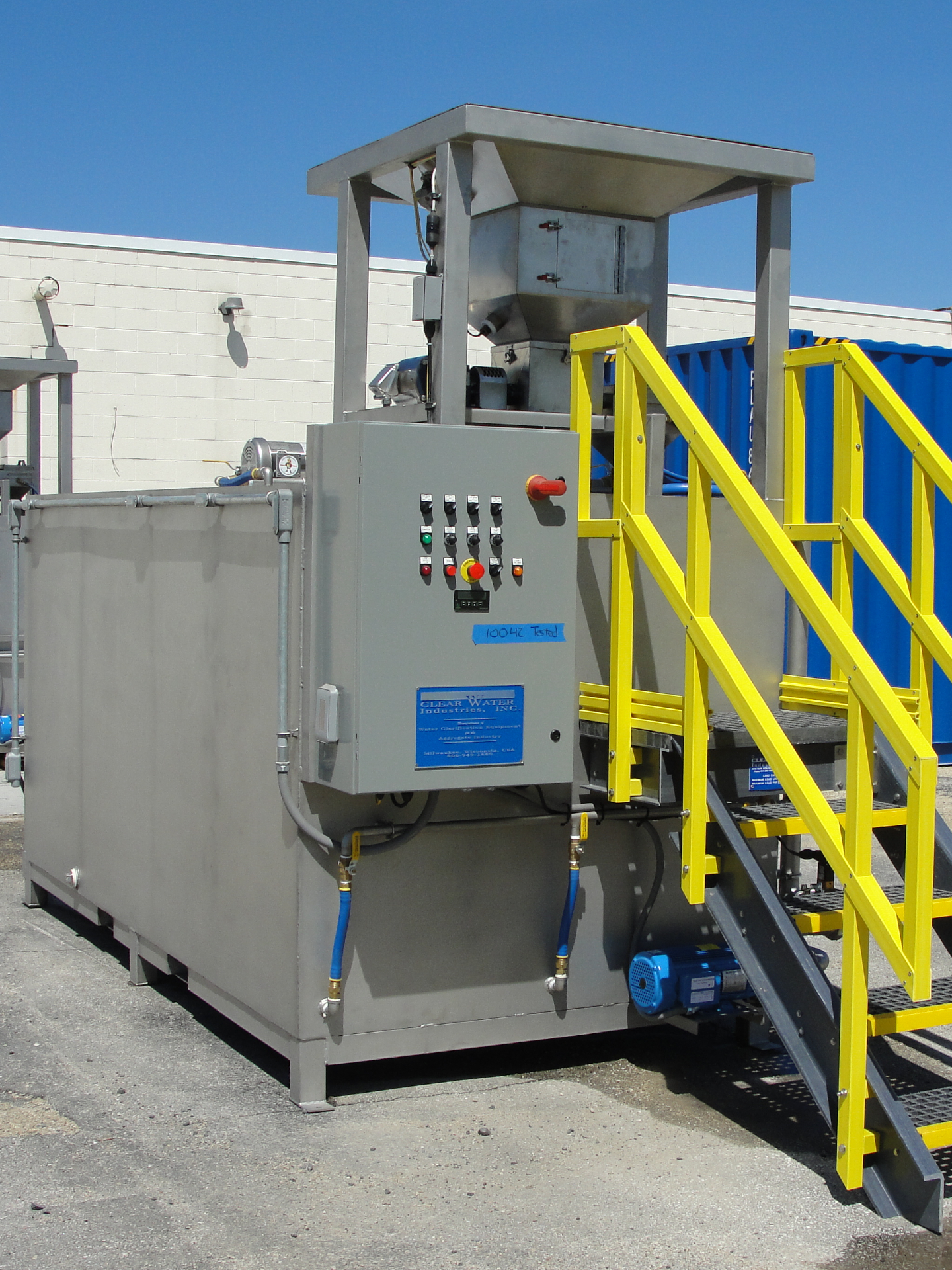 A large stainless steel dry polymer preparation system built to hold 1650 lbs. big bags pictured outside of a building.
