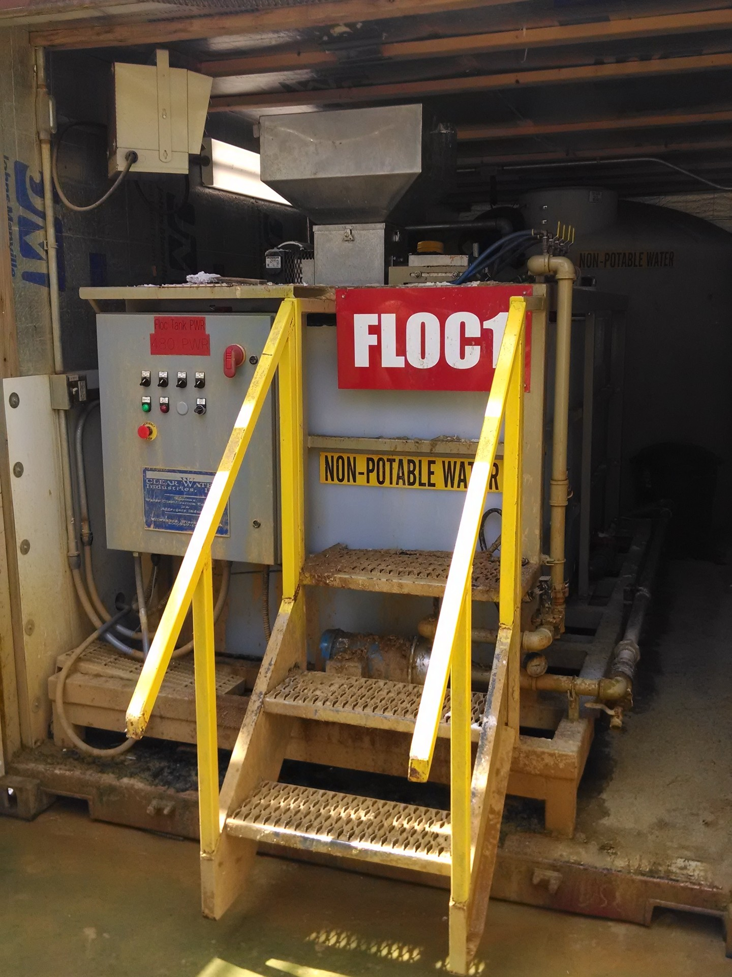An older and dirty dry polymer make-down system housed in a shipping container at an aggregate production site.