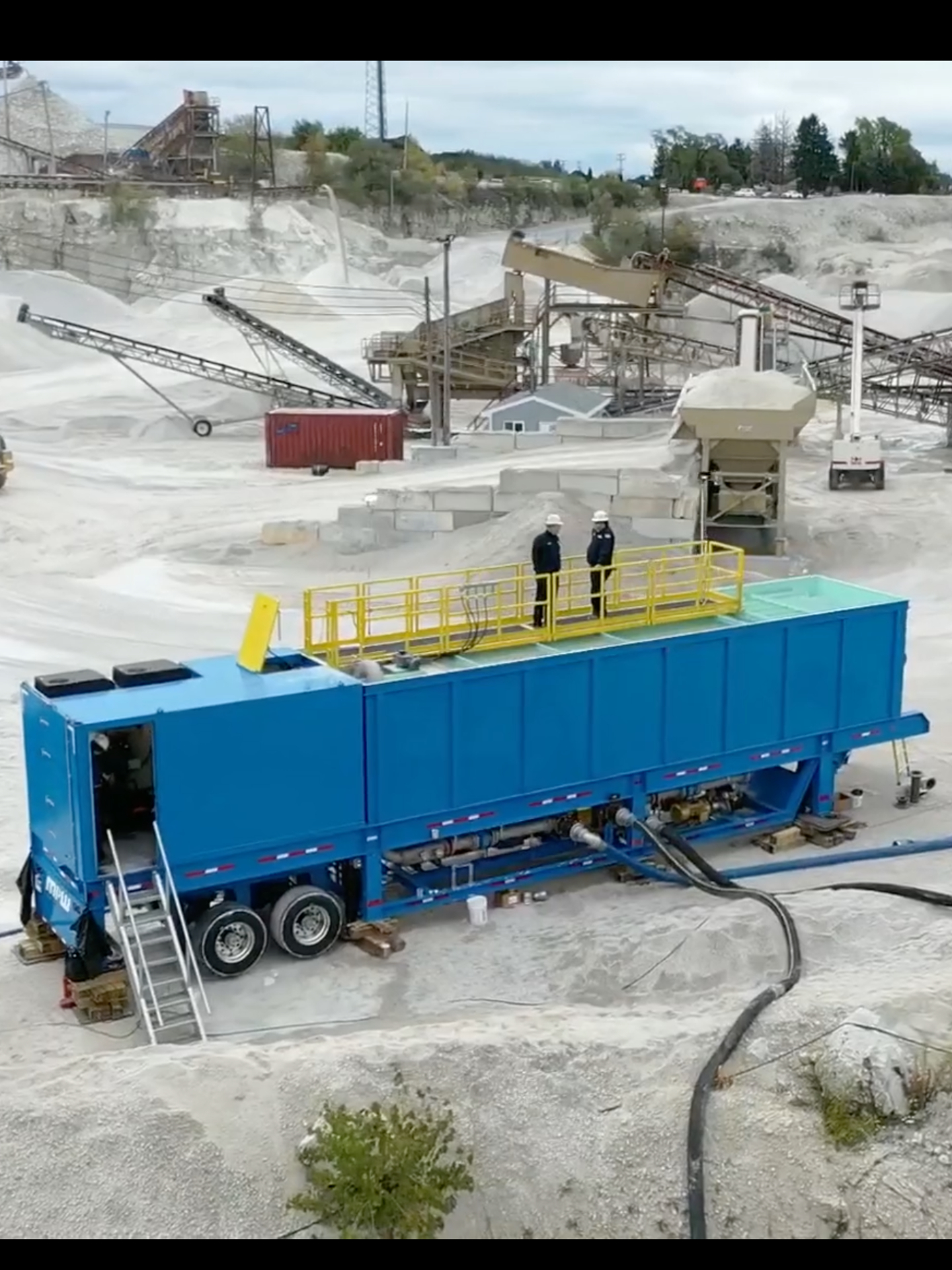 A rectangular portable industrial water clarifier setup at a quarry with two men standing on top of it.